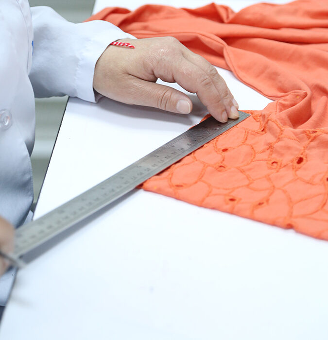 laboratory technician cutting fabric