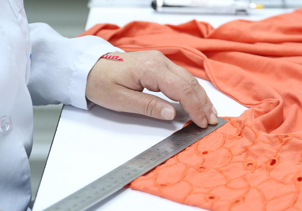 Orange textile being measured and cut in a conditioned laboratory