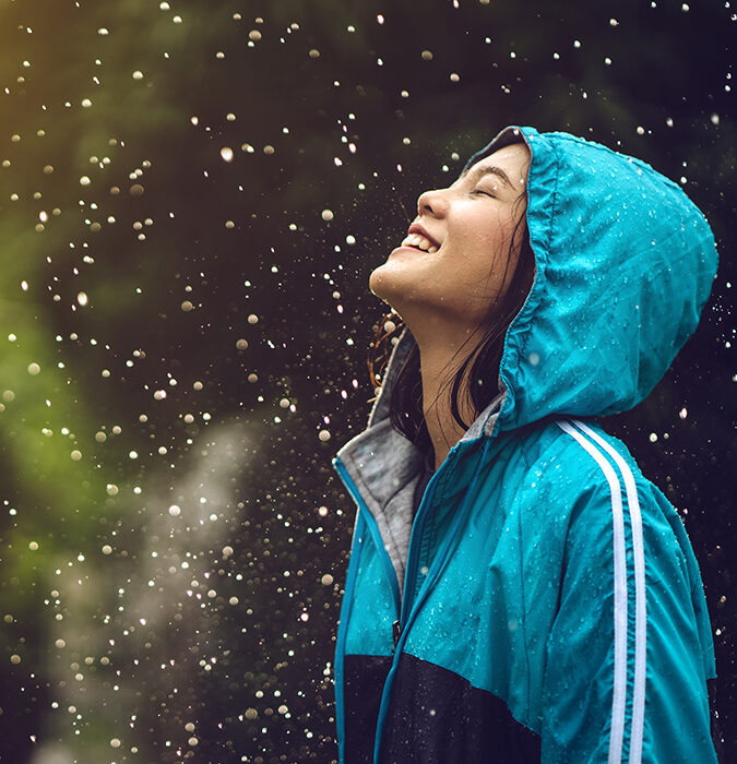 Person in coat smilng in the rain - application for testing on AquAbrasion