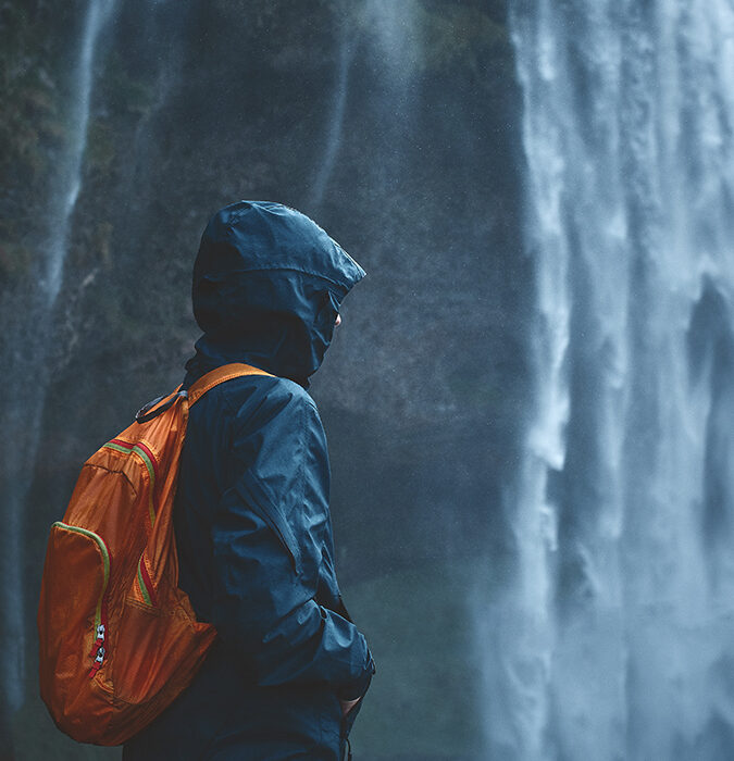 Person in raincoat by a waterfall - application for testing on AquAbrasion