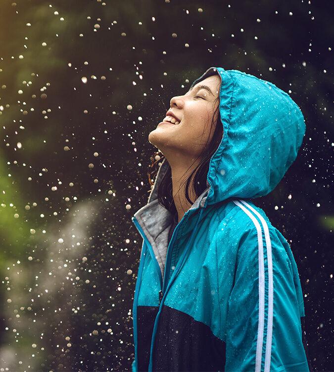 Lady in raincoat in rain aquabrasion application