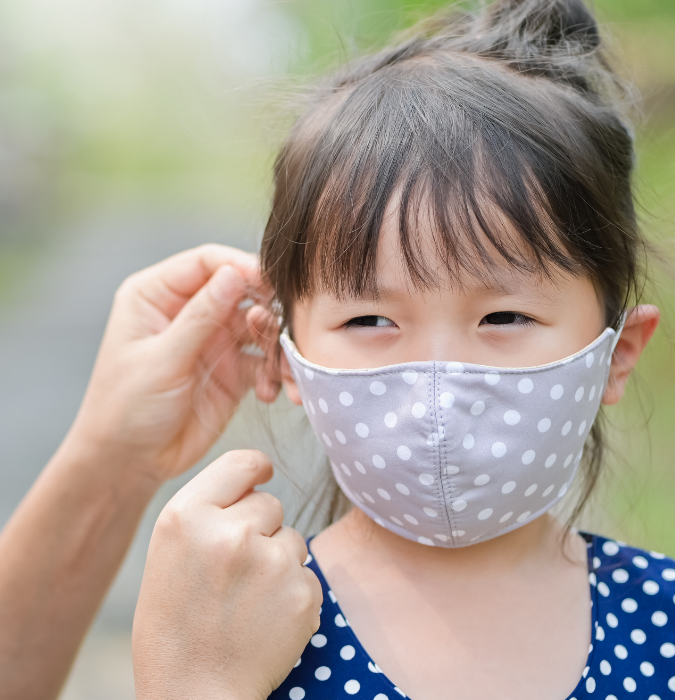 small child wearing a cloth face mask