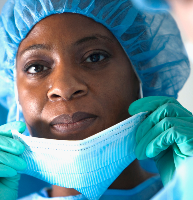 black woman surgeon in personal protective equipement ppe including hairnet and surgical mask