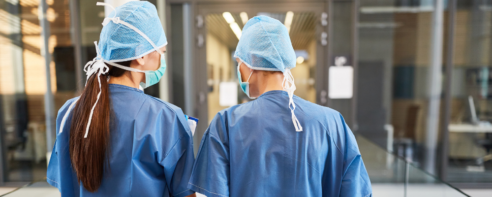 two surgeons facing backwards wearing personal protective equipment ppe including blue gowns