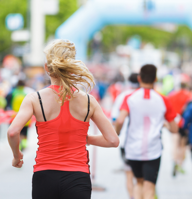woman running marathon, sweat wicking through her top