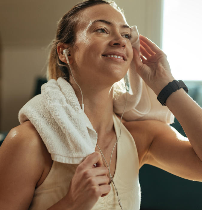 woman wiping sweat with a towel after gym