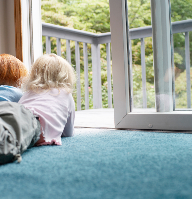 Two children by a window with sunshine on the carpet