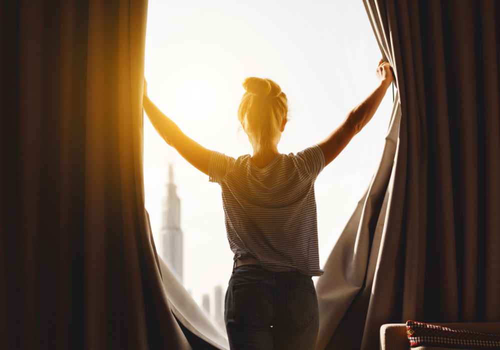 back of woman opening curtains to bright sunlight